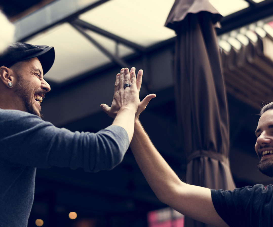 Two people high fiving with hands together