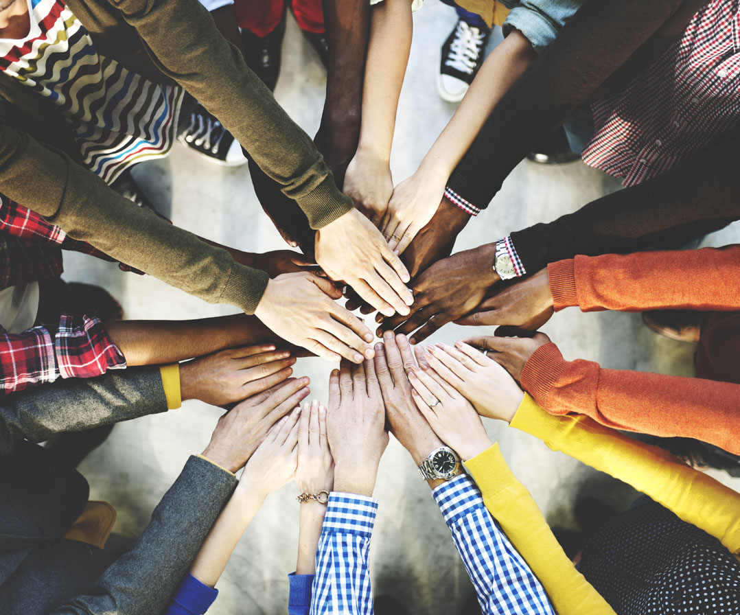 A group of people with their hands together in a circle